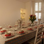 Cath Kidson inspired Dining room with enough place settings of china, crockery and glassware to seat 20